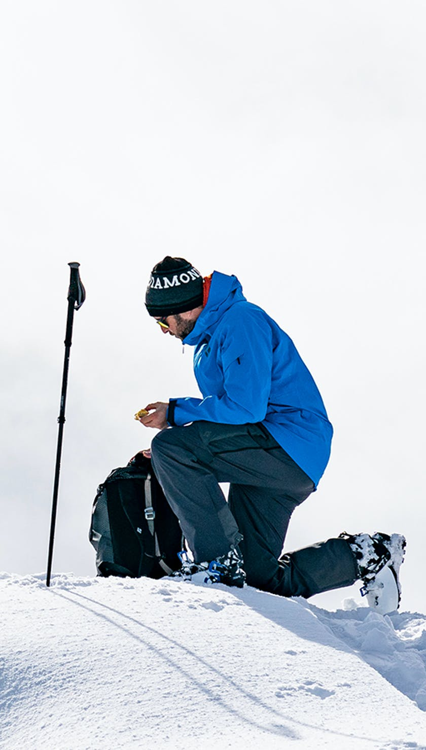 man getting his skis set up for a line