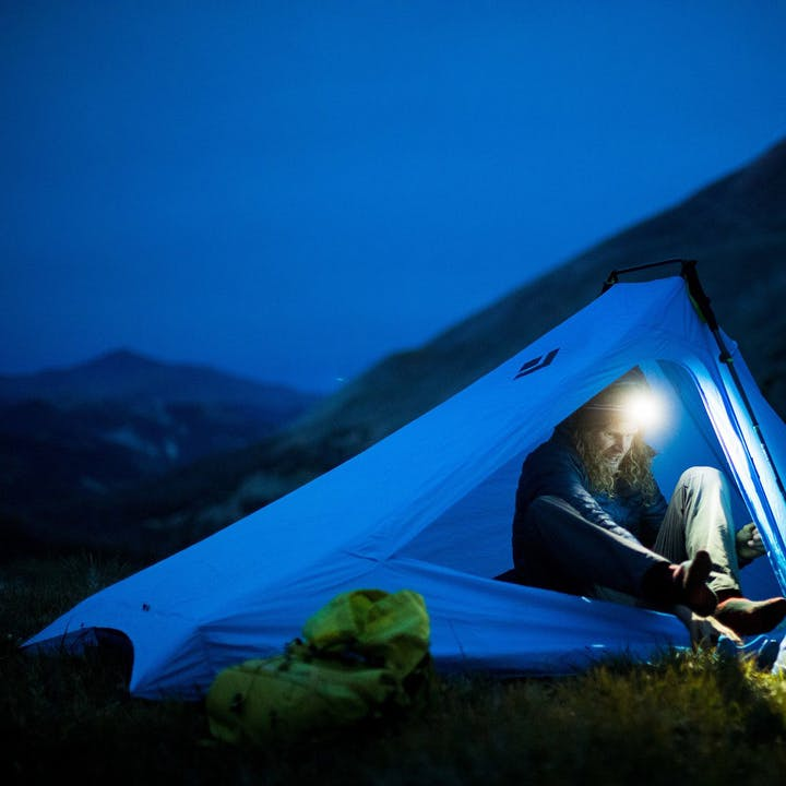 Photograph by Forest Woodward of Joe Grant in a tent before dawn