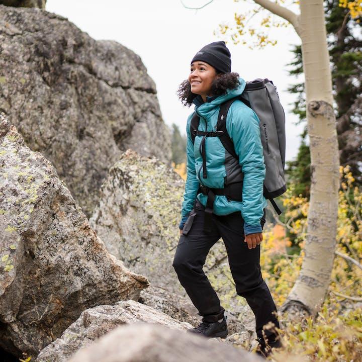 A hiker wearing the Black Diamond Women's Vision Hybrid Hoody.