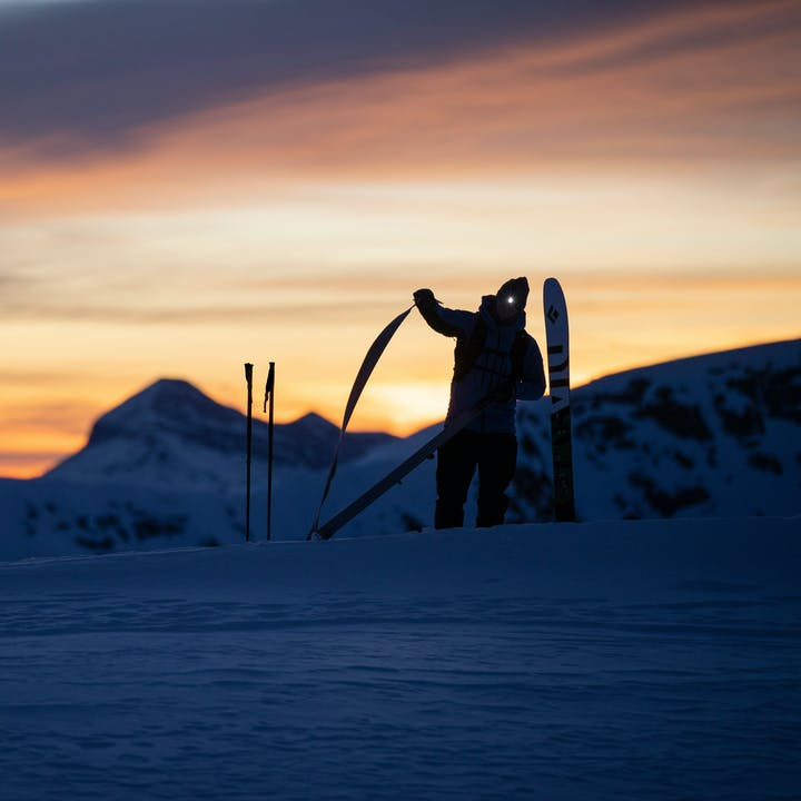 taking skins off skis at dusk