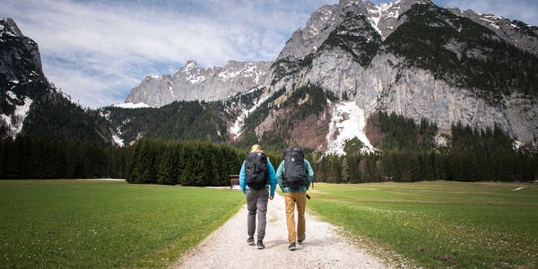 A photo by Andy Earl of two people walking in front of mountains