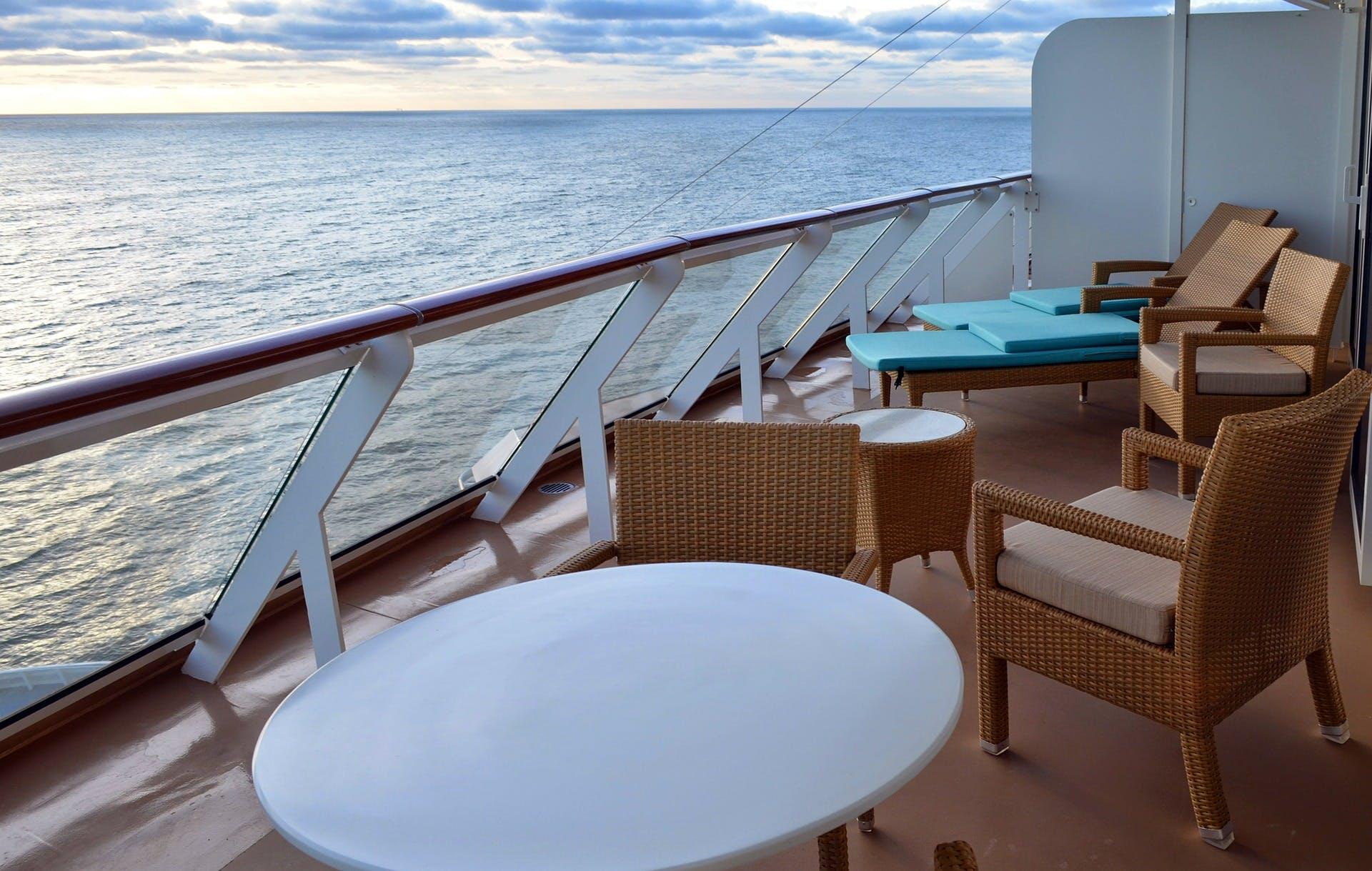 varanda privativa de um cruzeiro, com cadeiras e espreguiçadeiras