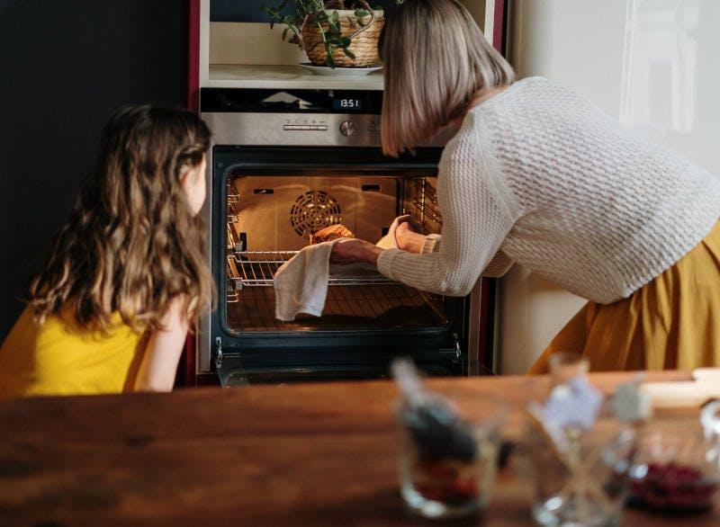 Mulher e criança retirando um alimento do forno embutido