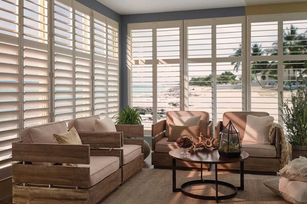 modern coastal sunroom with shutters overlooking the beach.