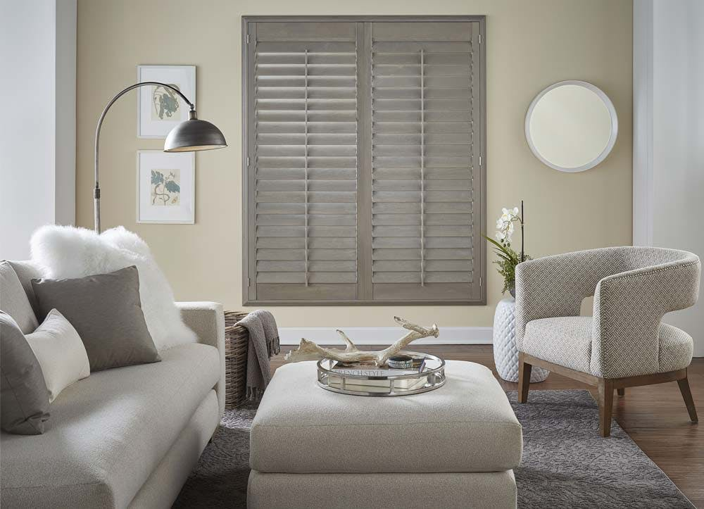 transitional living room with greige furniture and grey shutters.