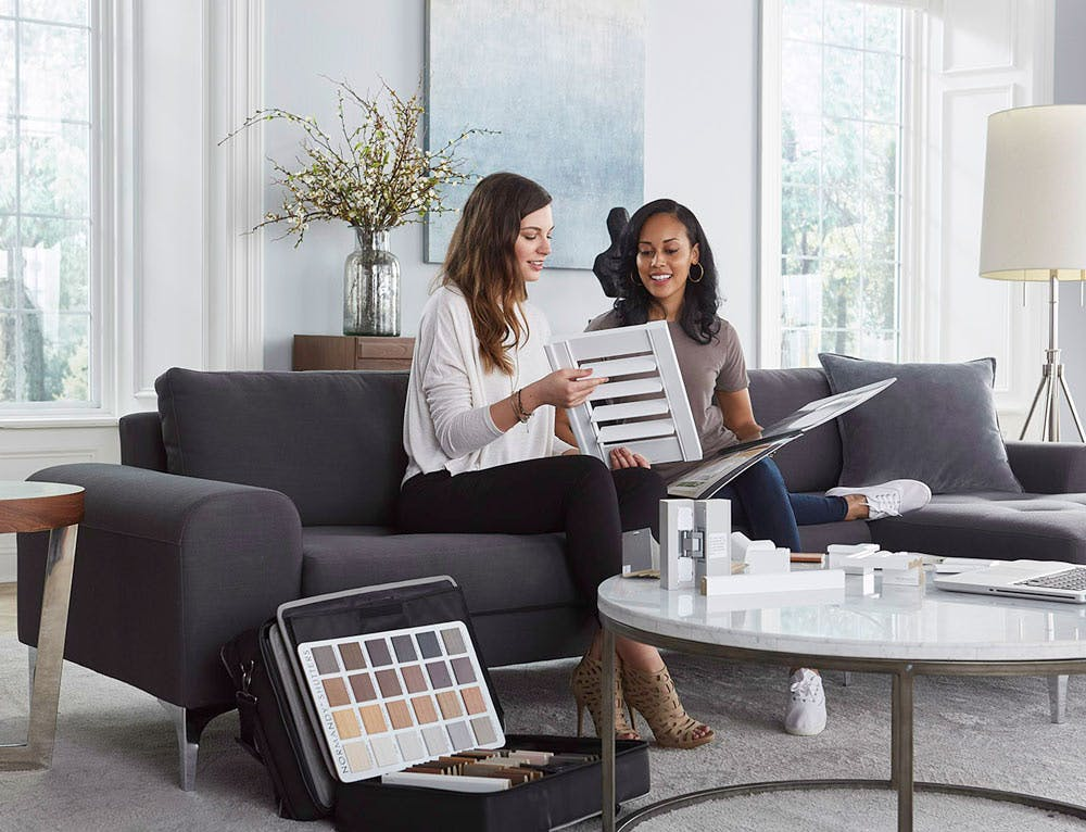 two women looking at shutter samples during an in home consultation.