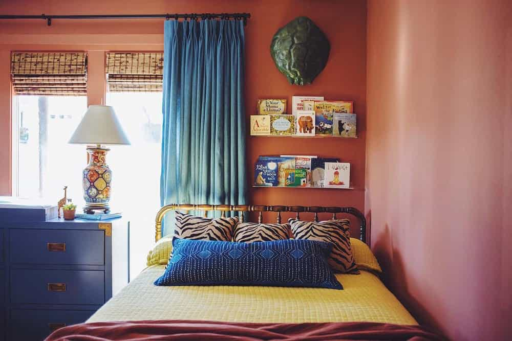 Terracotta toned kid's bedroom with vibrant blue draperies and woven wood shades.