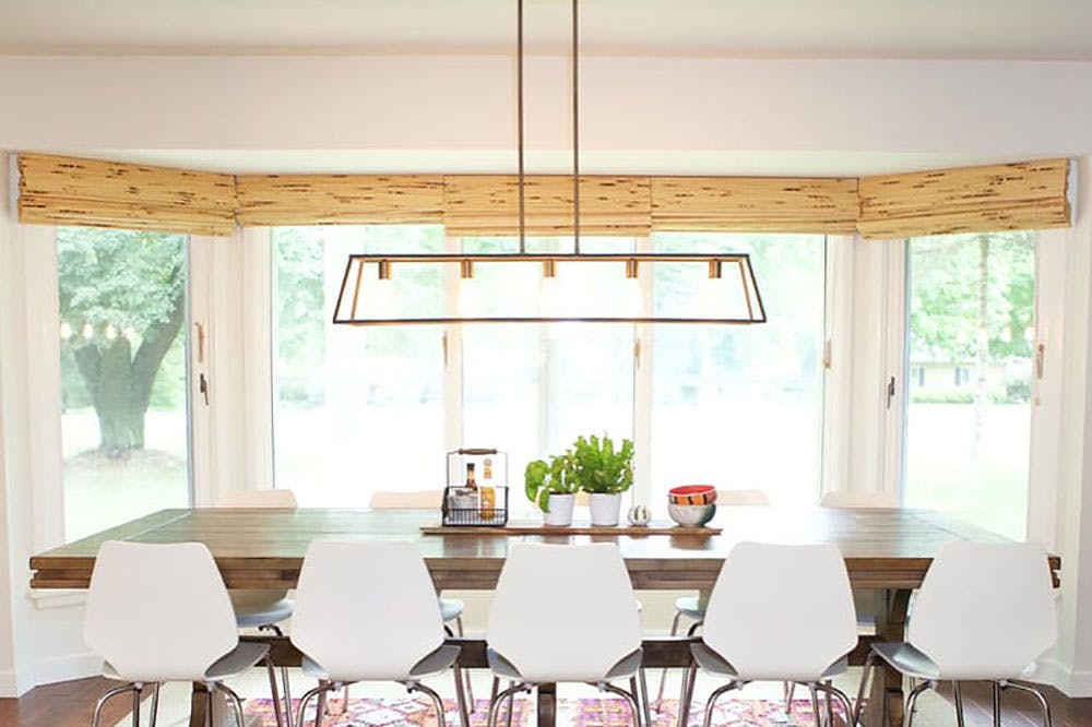 a large bay window in a dining room that is covered with woven wood shades.