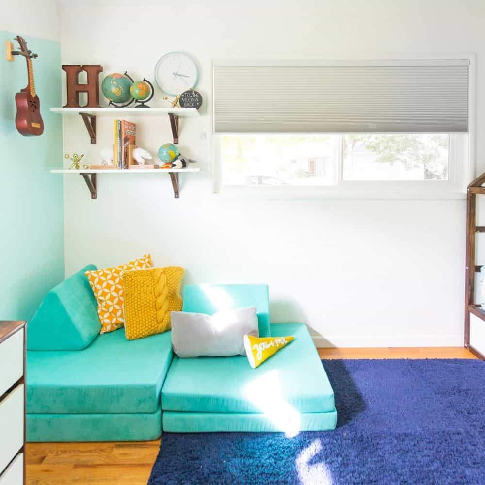 Kids bedroom corner with modular turquoise sofa, yellow pillows, shelf with different sized globes and a grey cellular shade in the window.