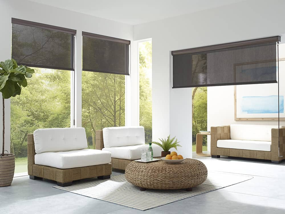 patio with modern woven furniture and black sun shades