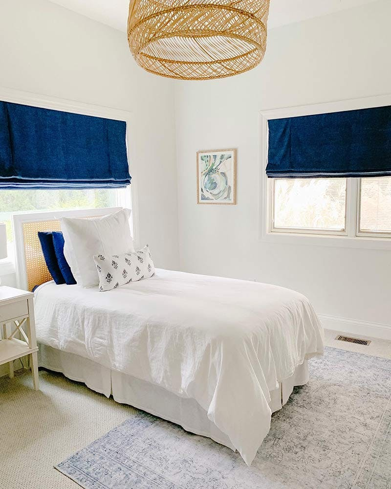 coastal bedroom with white walls and blue roman shades.