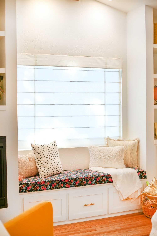 roman shade over window seat in bedroom
