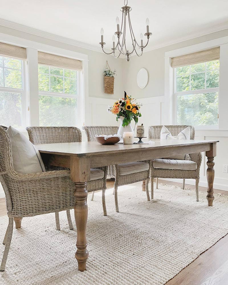 farmhouse styled dining room with tall windows and woven wood shades.