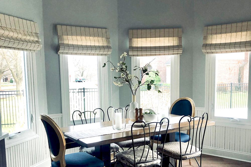 light blue dining room with bay windows covered with linen roman shades.