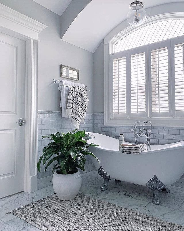 Traditional bathroom with shutters in an arch top window over a clawfoot tub.