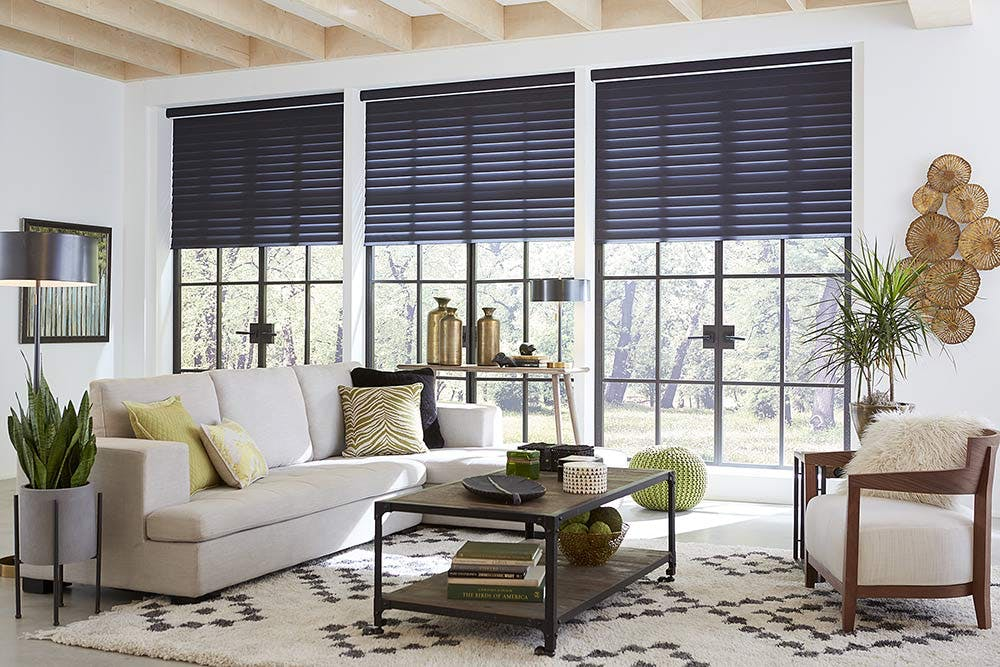 Contemporary living room with dark fabric blinds and beige furniture.