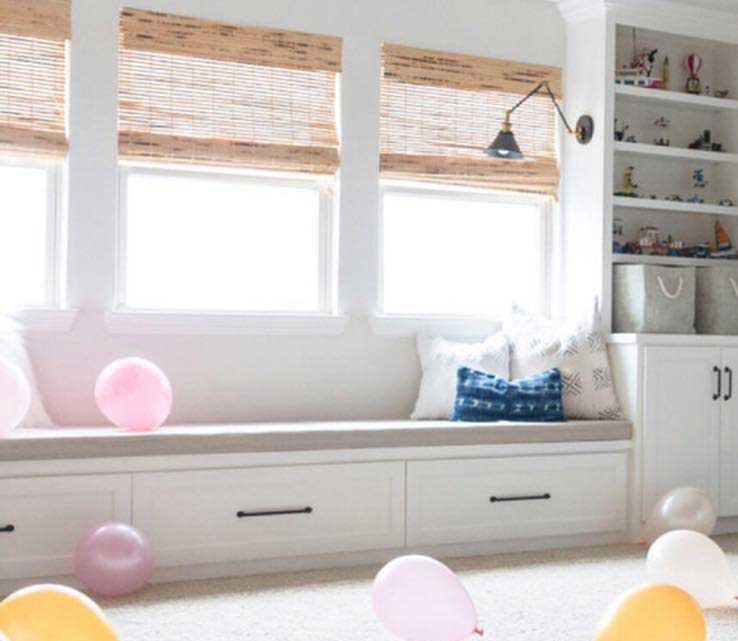 window seat in playroom with built in bookshelves