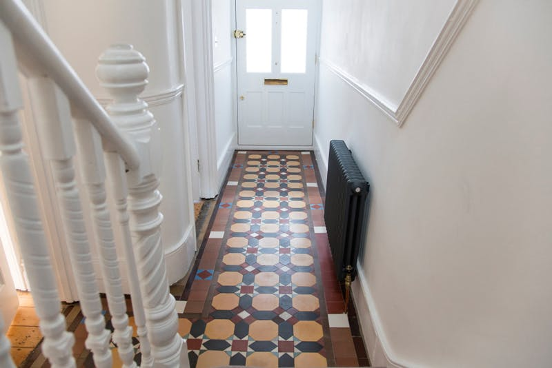 Hallway foyer with 70s inspired tile in brown and yellow.