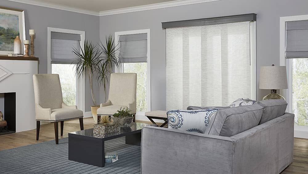 Grey living room with roman shades and sliding panel shades over sliding door