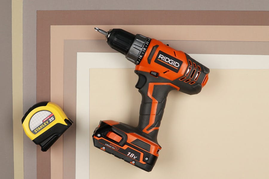 A tape measure and power drill/screwdriver on a neutral background.