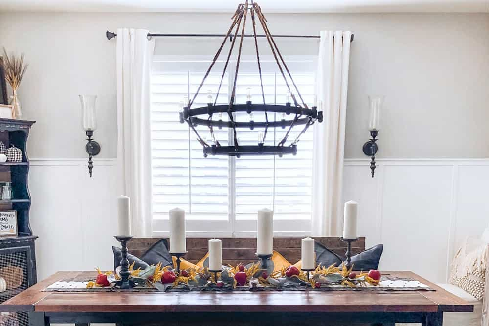 Modern farmhouse dining room decorated for fall with shutters in window.
