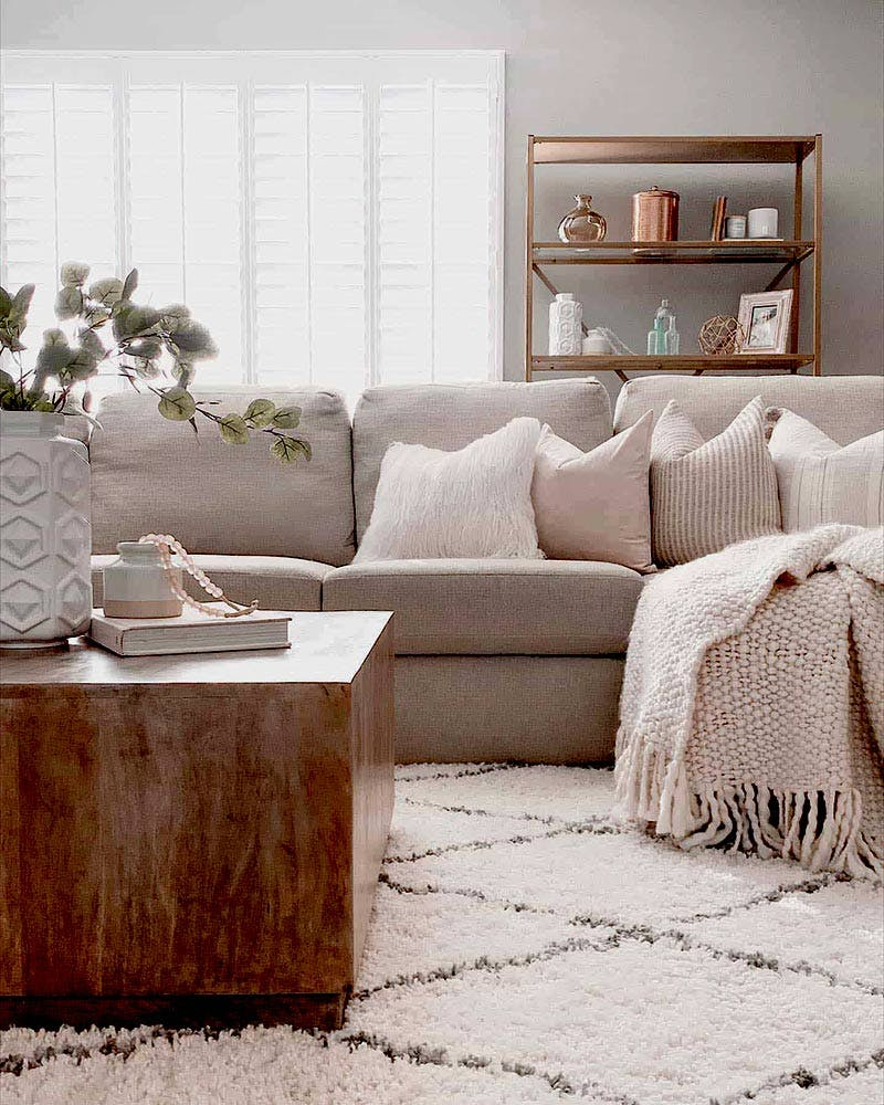contemporary and feminine living room with beige sofa and white plantation shutters in the window.