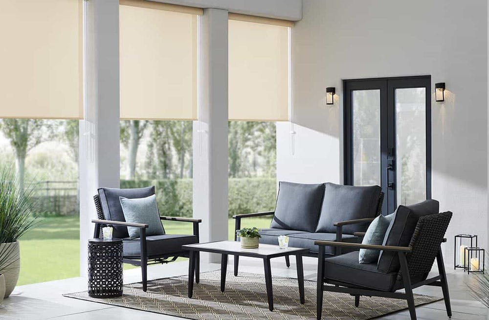 outdoor patio with grey, cushioned chairs around a coffee table and beige solar shades shielding the chairs from direct sun.