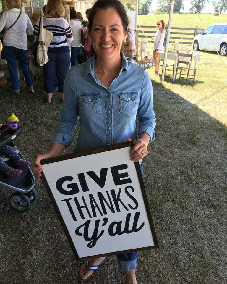 """Susie Harris holding """"Give thanks y'all"""" sign"""