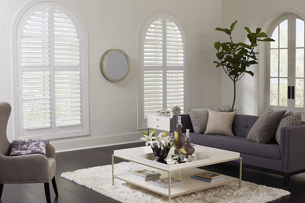 arched windows in living room with arch plantation shutters