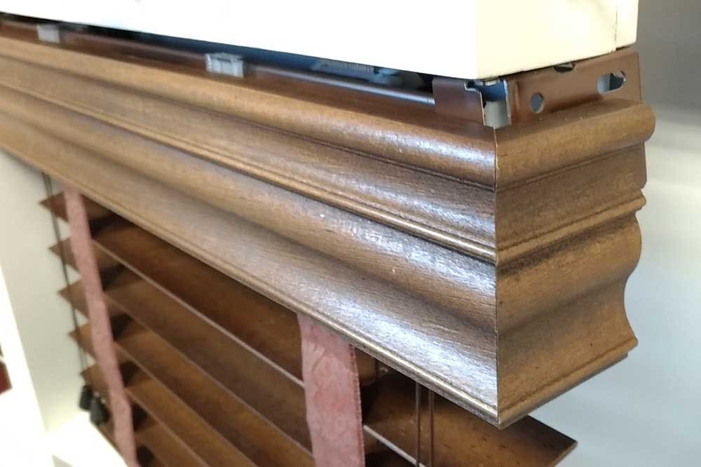 A wood blind with a valance that includes side returns to hide exposed hardware.