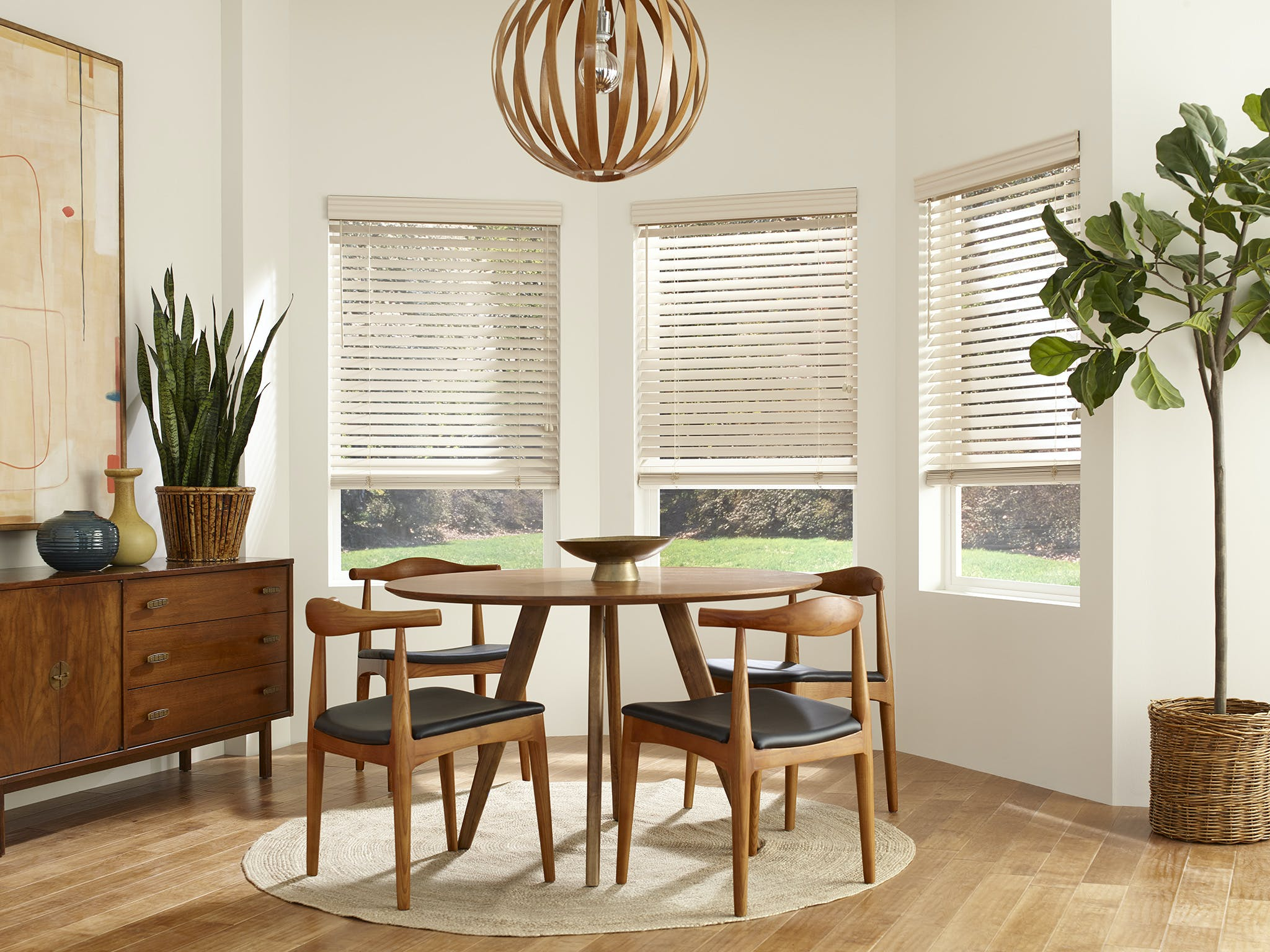Mid-century modern themed dining room with wood furniture and off-white wood blinds in the bay window.