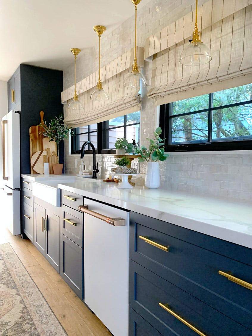 blue and white kitchen with brass hardware and roman shades over black windows