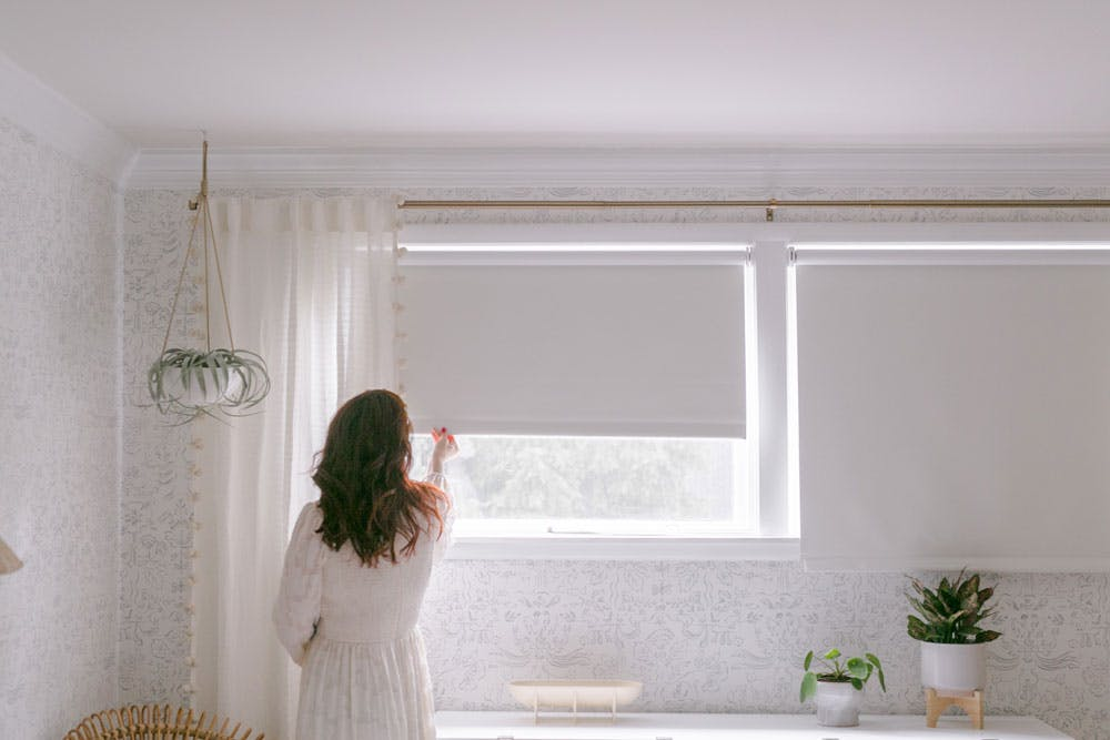 woman lowering cordless white blackout roller shades in neutral bedroom