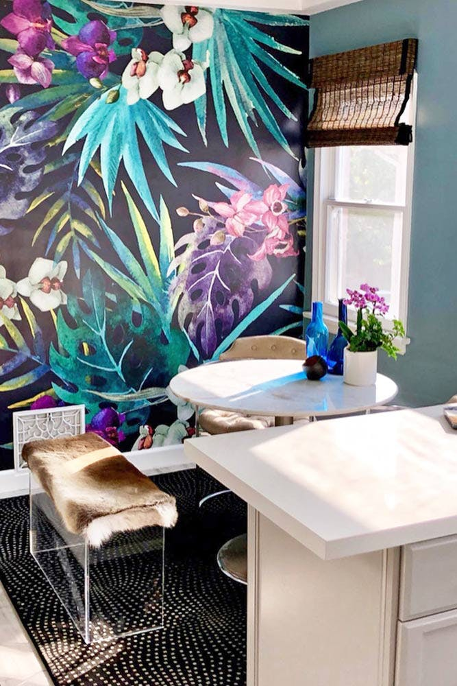bright, blue dining nook with tropical themed wallpaper accent wall and woven wood shades.