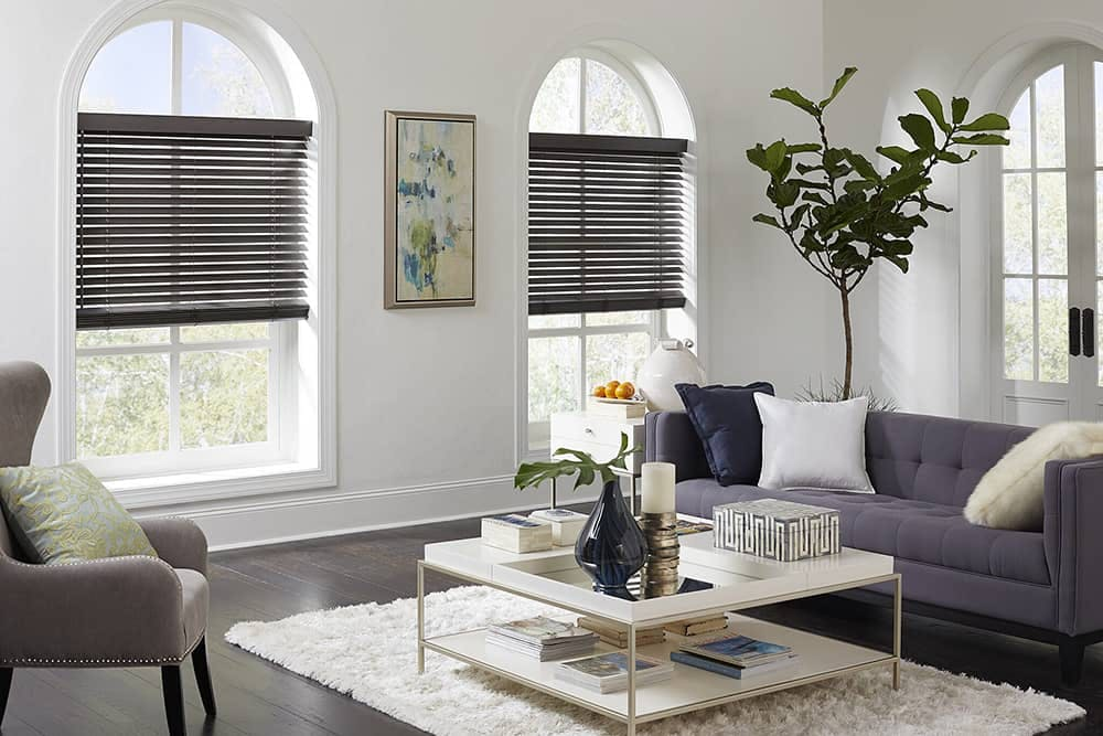 living room with arched windows and black wood blinds