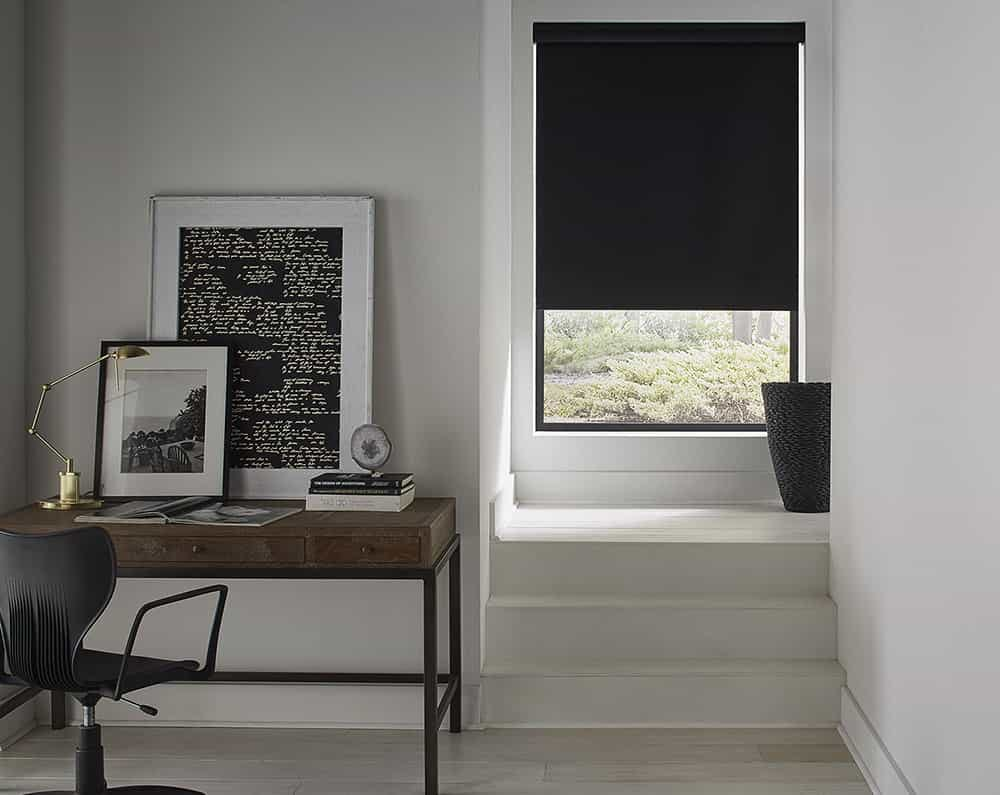Modern office with black accents and black roller shade in the hallway window.