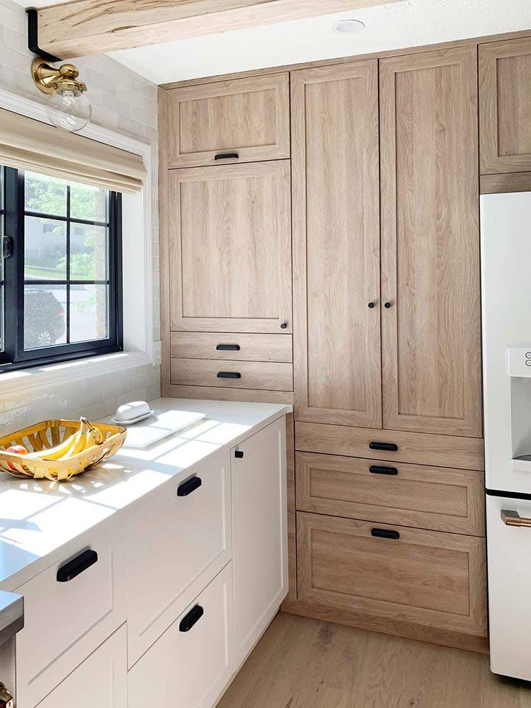 modern kitchen with light wood toned cabinets that match the floors and woven wood window shades.