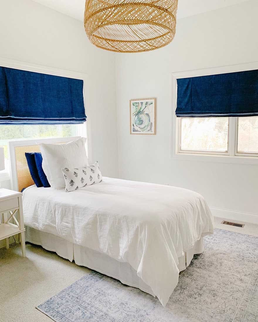 crisp, white, beachy bedroom with blue accent pillows and royal blue roman shades.