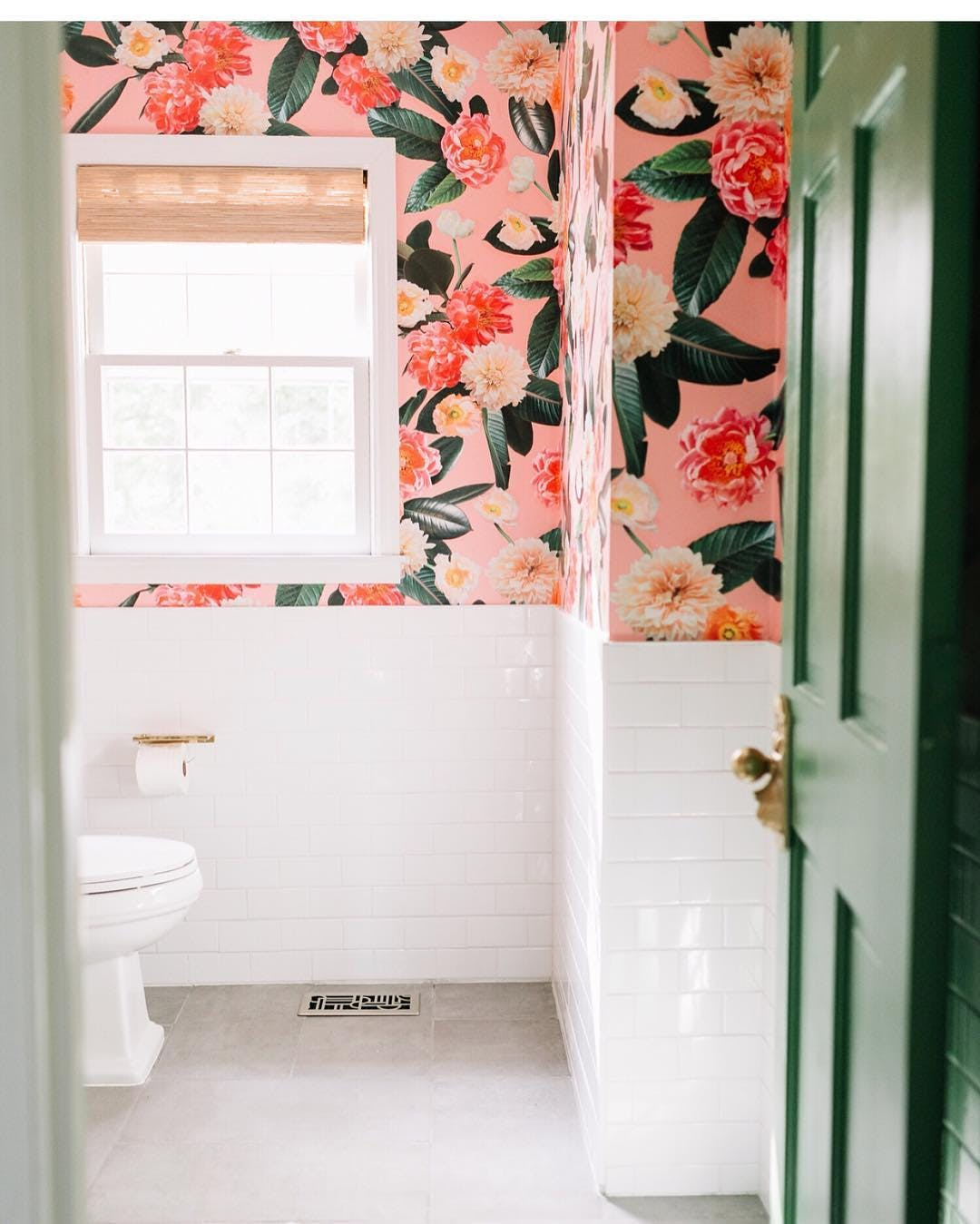 bathroom with pink tropical print wallpaper and white subway tile.