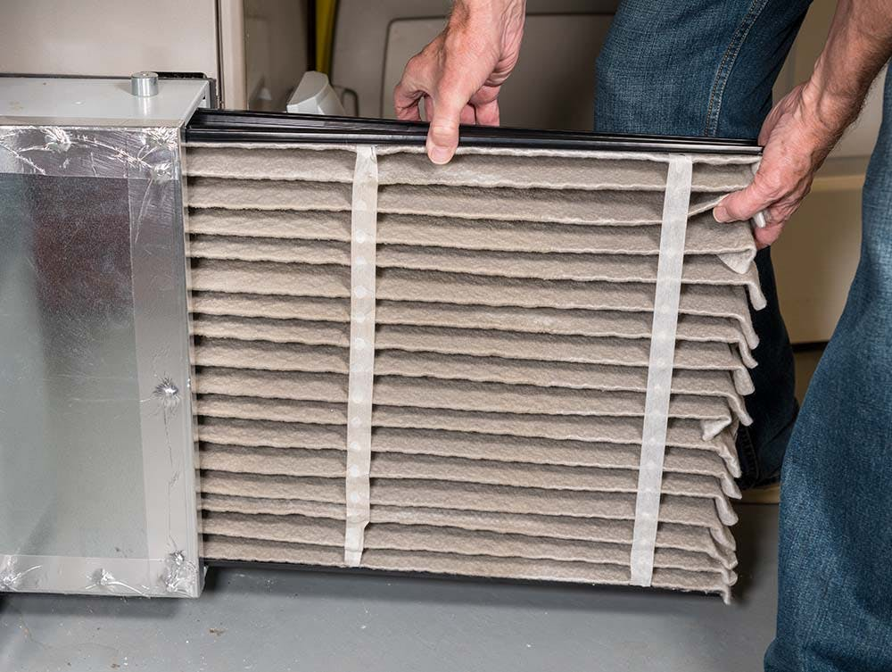 A man pulls a dirty air filter out of an air conditioning unit.