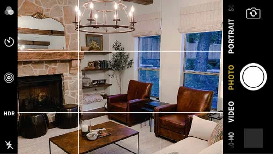 contemporary living room with chandelier and leather chairs. photo has grid overlay like it's being viewed through a camera phone.