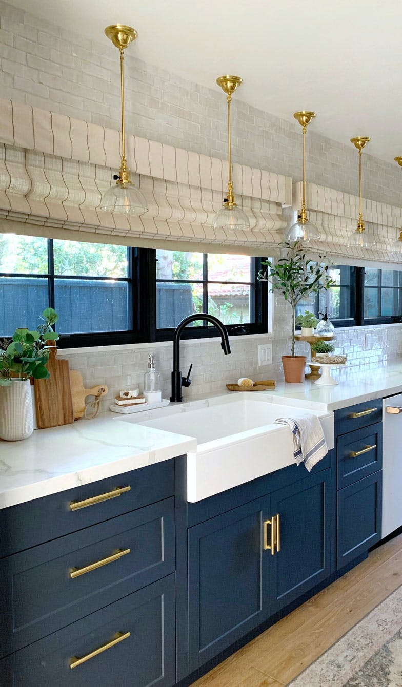 long bank of windows above kitchn counter with motorized roman shades