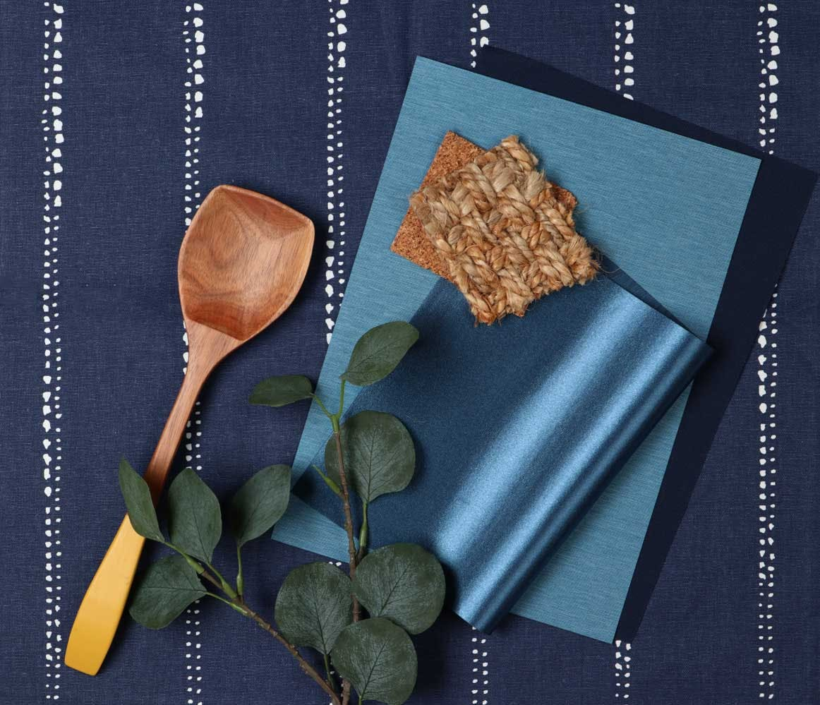 Deep blue fabric samples arranged in a flatlay with wood, cork and sisal accents.