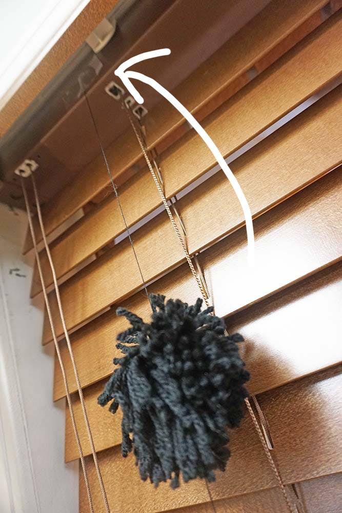 Close up showing pom pom strands are taped to the headrail of the blind and not the valance.