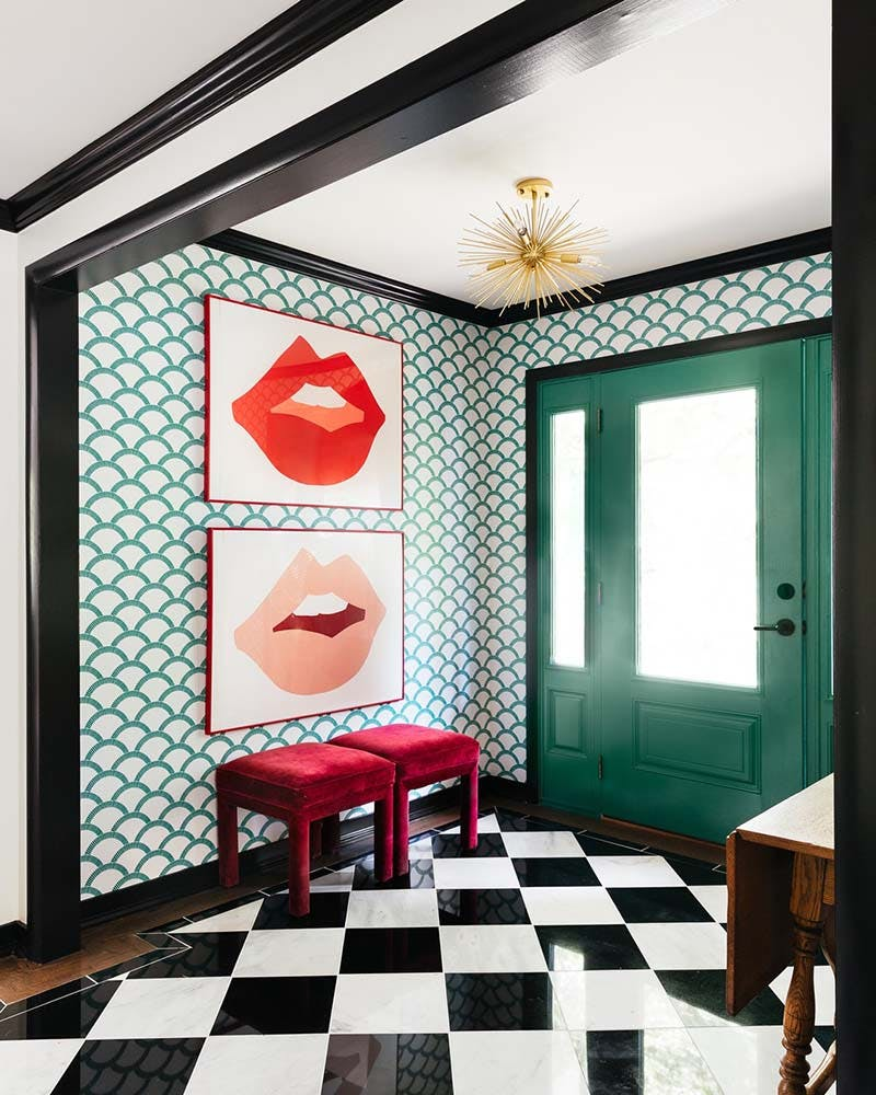 Colorful 70s art deco inspired foyer with black crown molding and marble checkered tile.