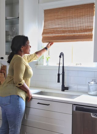 woman opening cordless woven wood shades behind kitchen sink