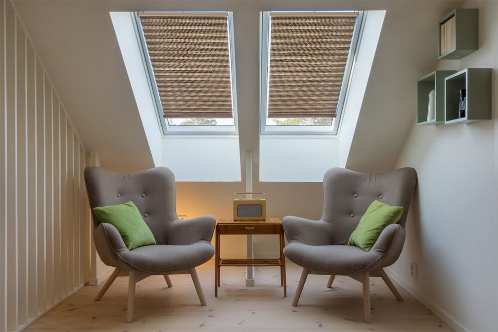 Angled ceiling with two skylight windows and pleated shades over a nook with two mid-century modern, grey fabric chairs.