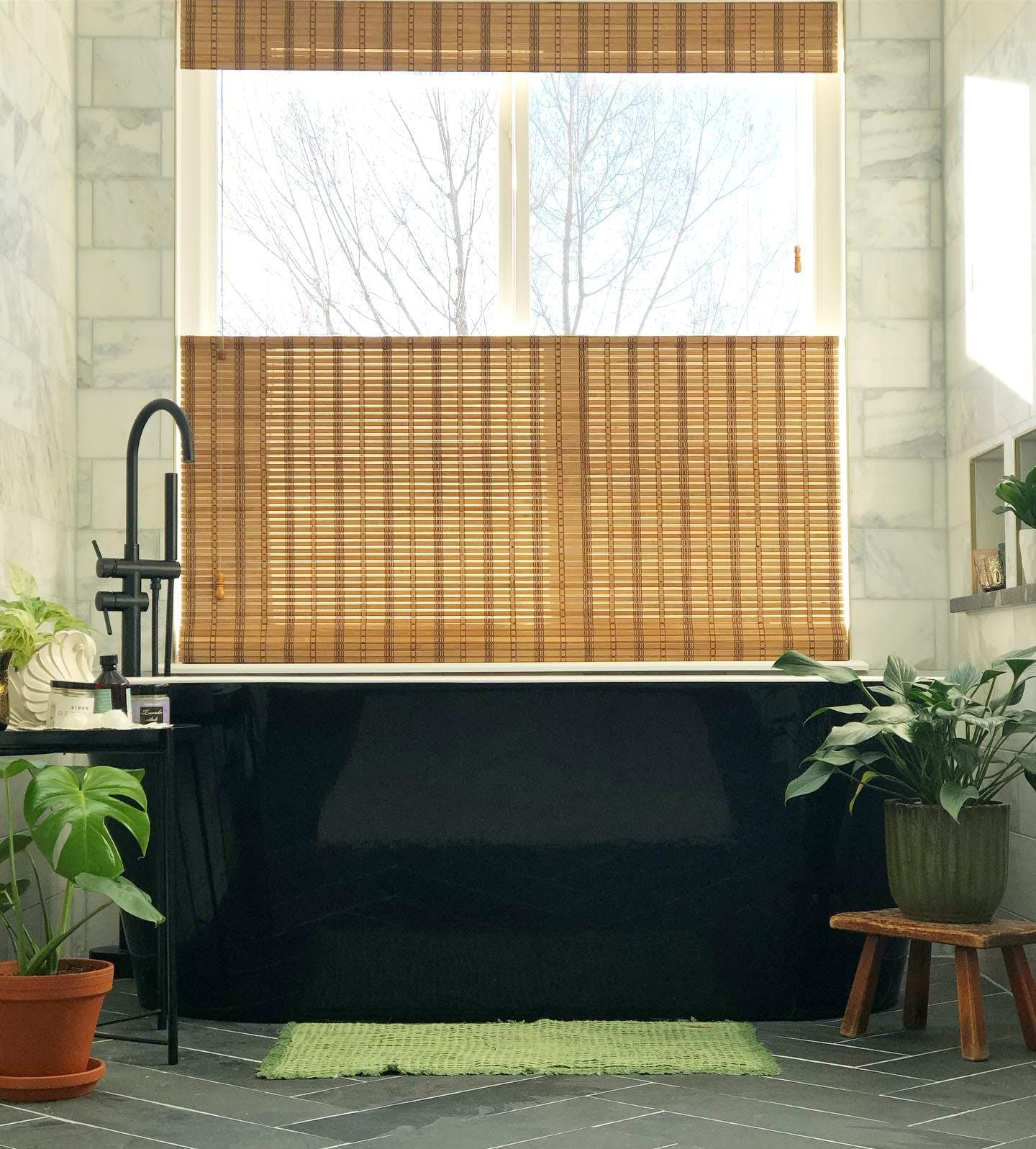 Large, black, free standing tub next to a window with a woven wood shades and surrounded by plants.