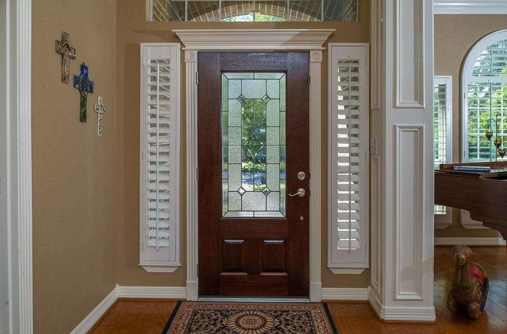 Front door with white shutters over the sidelight windows on each side.