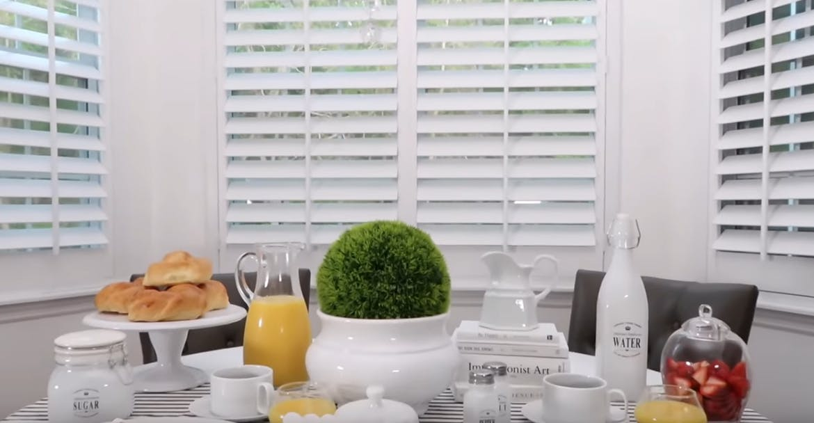 breakfast table set with brunch in front of bay window shutters